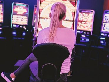Blonde playing at a slot machine
